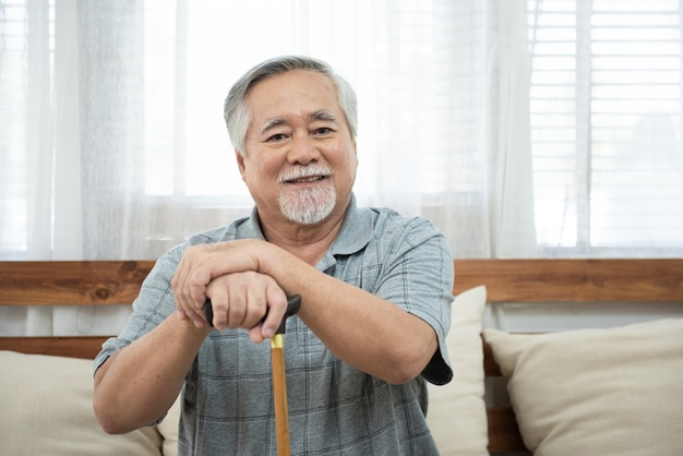 Portrait of senior elderly asian man sit on coach hand hold walking stick look at camera with smile. Premium Photo