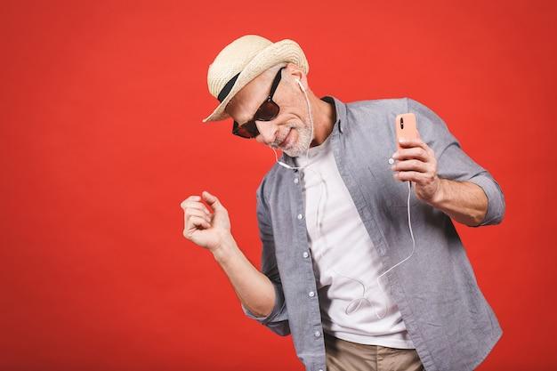 Portrait of senior happy cheerful elderly man dancing and listening music witn phone and headphones  isolated. Premium Photo