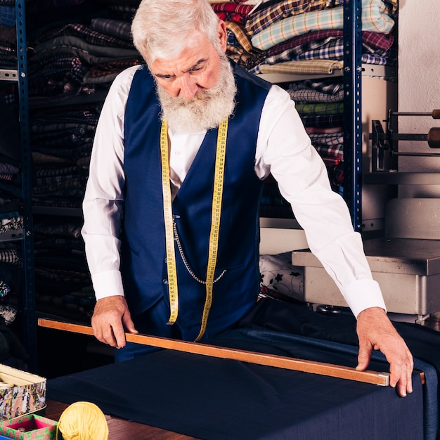 Portrait of a senior male fashion designer measuring fabric with wooden ruler Free Photo