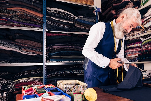 Portrait of a senior male tailor cutting a piece of fabric with scissors Free Photo