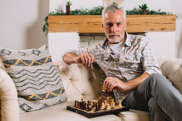 Portrait of a senior man sitting on sofa playing chess Free Photo