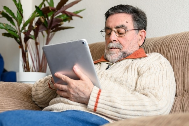 Portrait of senior man sitting on sofa and using digital tablet in living room. Premium Photo