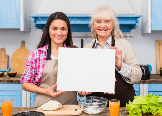 Portrait of senior mother and her young daughter holding blank white card standing in the kitchen Free Photo