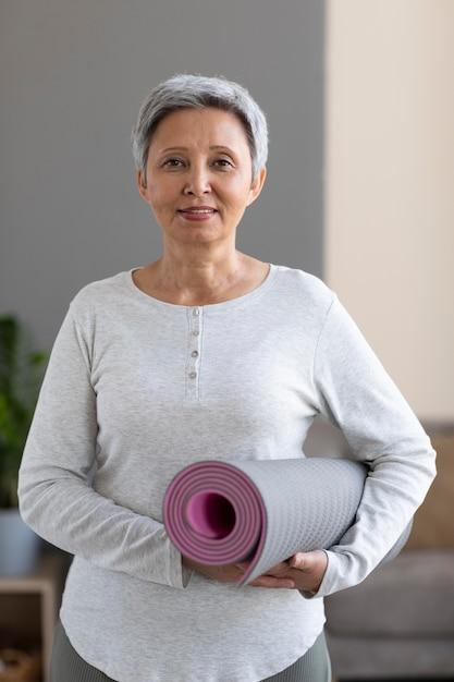 Portrait of senior woman holding yoga mat Free Photo