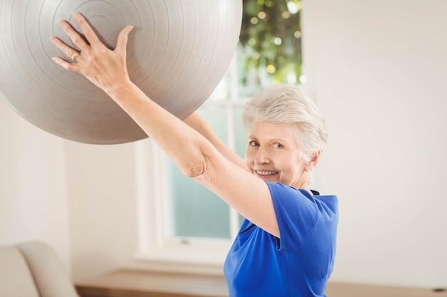Portrait of senior woman lifting exercise ball while exercising at home Premium Photo