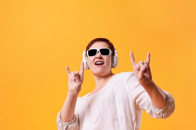 Portrait of senior woman listening rock music Free Photo