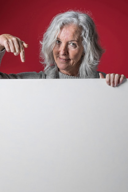 Portrait of a senior woman pointing her finger downward the white blank placard Free Photo