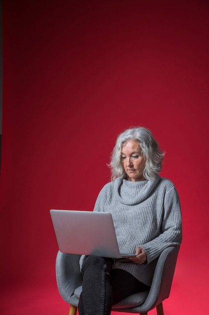 Portrait of a senior woman sitting on armchair using the laptop against red background Free Photo