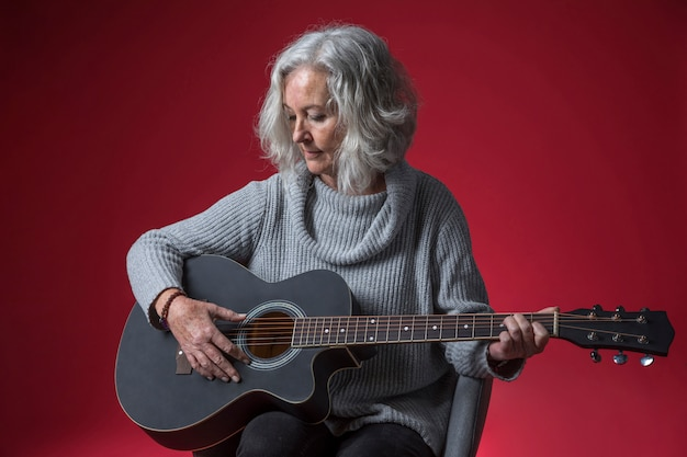 Portrait of a senior woman sitting on chair playing the guitar against red background Free Photo
