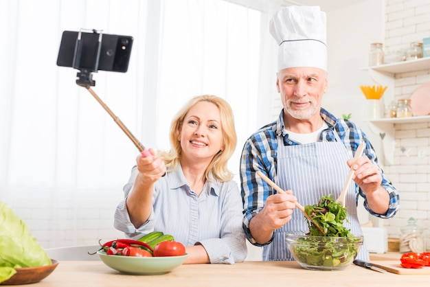 Portrait of a senior woman taking selfie on mobile phone with her husband preparing the salad in the kitchen Free Photo