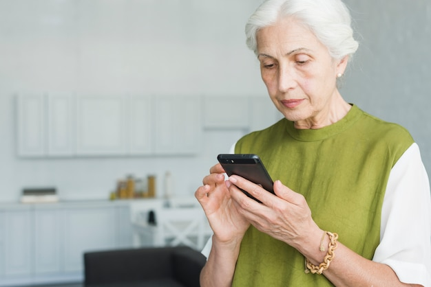 Portrait of senior woman texting on cell phone at home Free Photo