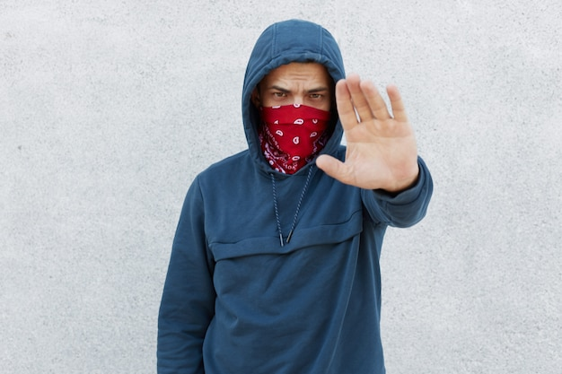 Portrait of serious disappointed protester against black citizens lawlessness,guy showing stop gesture with his palm, stop murder people, activist wearing jumper with hoody and bandana mask. Free Photo