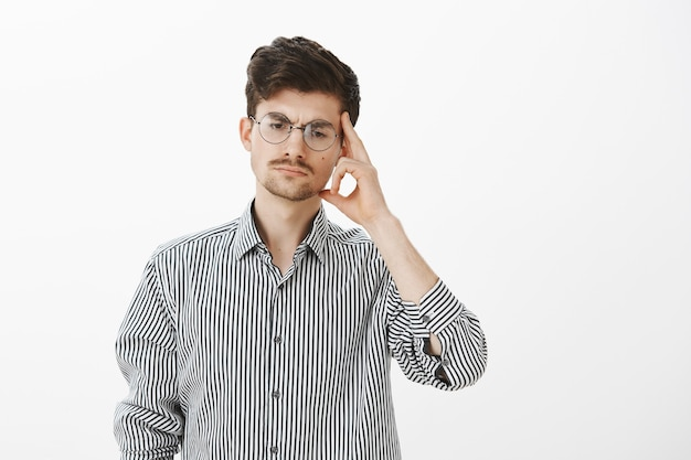 Ritratto di un collega maschio serio concentrato in occhiali rotondi, guardando in basso e tenendo la tempia con il dito indice, concentrandosi mentre pensa, preparando un piano su come evitare situazioni scomode Foto Gratuite
