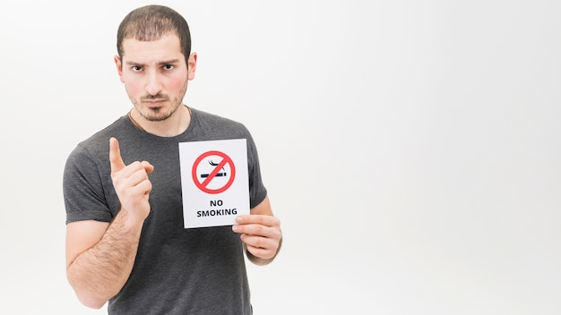 Portrait of a serious man holding no smoking sign pointing finger toward camera Free Photo