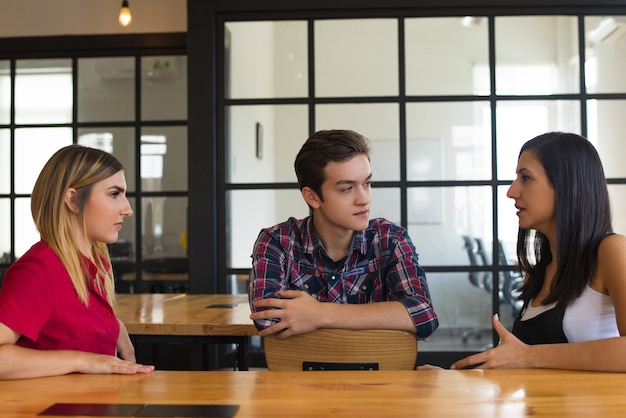 Portrait of serious student friends sitting at table and talking Free Photo
