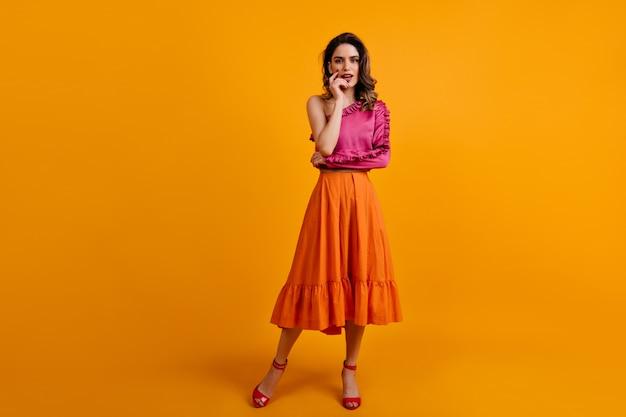 Portrait of serious woman wears long orange skirt Free Photo