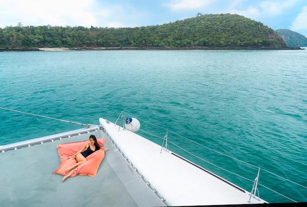 Portrait sexy asian girl in nice black bikini lay down relaxing on bean bag in part of cruise yacht. Premium Photo
