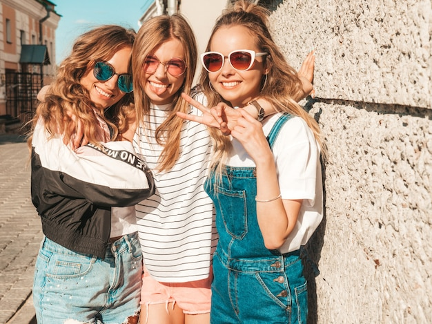 Portrait of  sexy carefree women posing near wall in the street.positive models having fun in sunglasses Free Photo