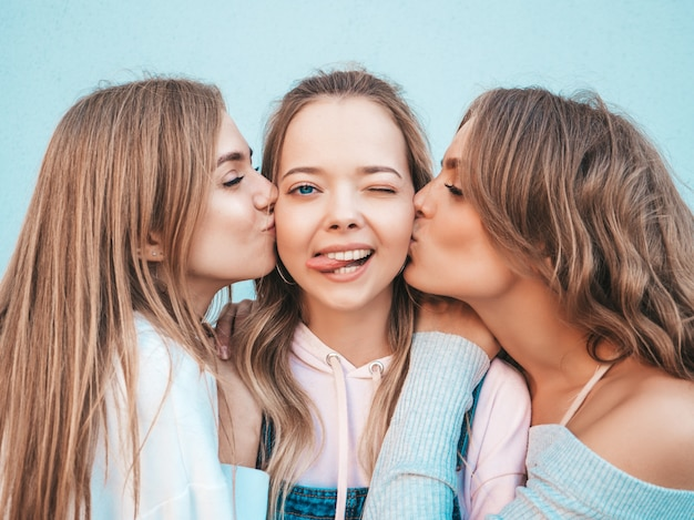 Portrait of  sexy carefree women posing in the street.positive models kissing their friend in cheek Free Photo