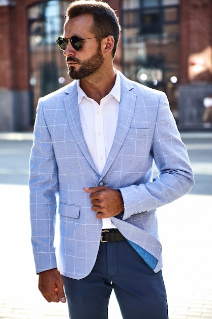Portrait of sexy handsome fashion businessman model dressed in elegant blue suit posing on street background. metrosexual Free Photo