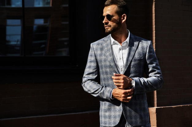 Portrait of sexy handsome fashion businessman model dressed in elegant checkered suit posing on street background. metrosexual Free Photo