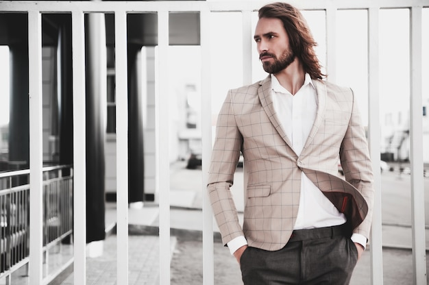 Portrait of sexy handsome fashion male model man dressed in elegant beige checkered suit posing on the street background Free Photo