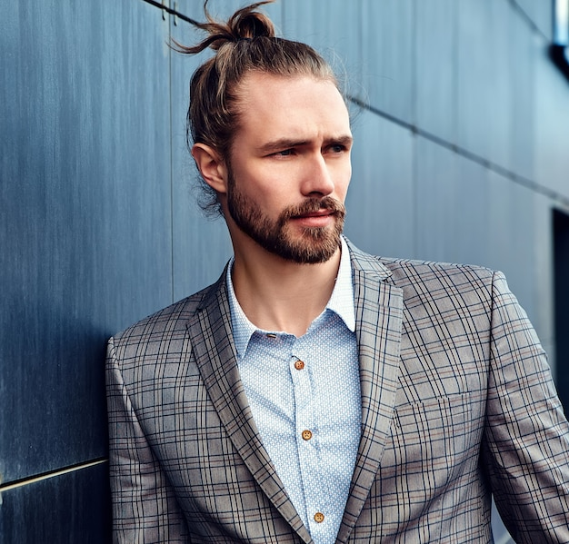Portrait of sexy handsome fashion male model man dressed in elegant checkered suit posing near dark blue wall in the street background; Free Photo