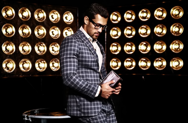 Portrait of sexy handsome fashion male model man dressed in elegant suit on black studio lights background in glasses Free Photo