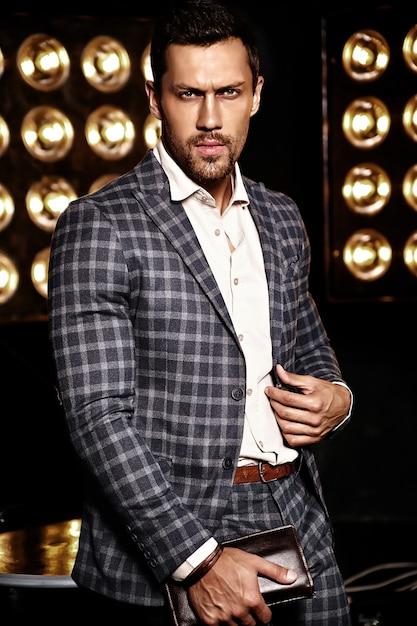 Portrait of sexy handsome fashion male model man dressed in elegant suit on black studio lights background Free Photo