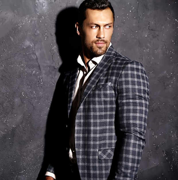 Portrait of sexy handsome fashion male model man dressed in elegant suit posing near gray wall Free Photo