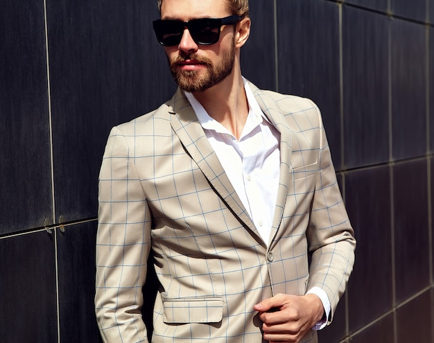 Portrait of sexy handsome man dressed in elegant beige checkered suit Free Photo