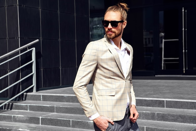Portrait of sexy handsome man dressed in elegant beige checkered suit Free Photo