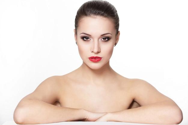 Ritratto di modello di giovane donna caucasica sexy seduta seria con labbra rosse glamour, trucco luminoso, trucco della freccia dell'occhio, carnagione di purezza. pelle pulita e perfetta Foto Gratuite