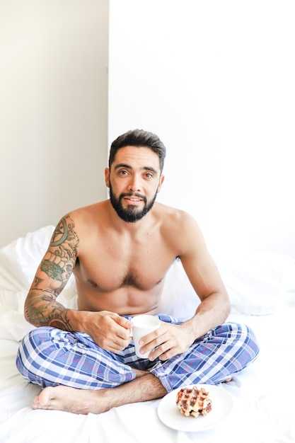 Portrait of a shirtless man sitting on bed with cup of coffee and waffle on plate Free Photo