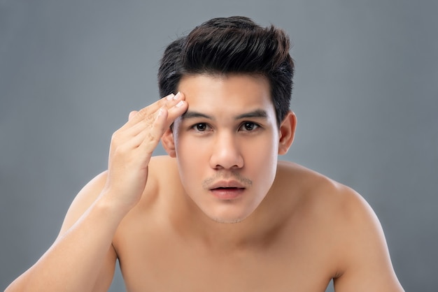Portrait of shirtless young handsome asian man checking his face skin Premium Photo