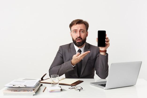 Ritratto di uomo d'affari barbuto attraente scioccato, manager seduto al desktop in ufficio, guardando la telecamera incredulo, vestito con un vestito costoso con una cravatta, indicando il suo smartphone. Foto Gratuite
