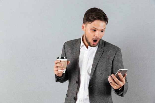 Portrait of a shocked businessman looking at mobile phone Free Photo