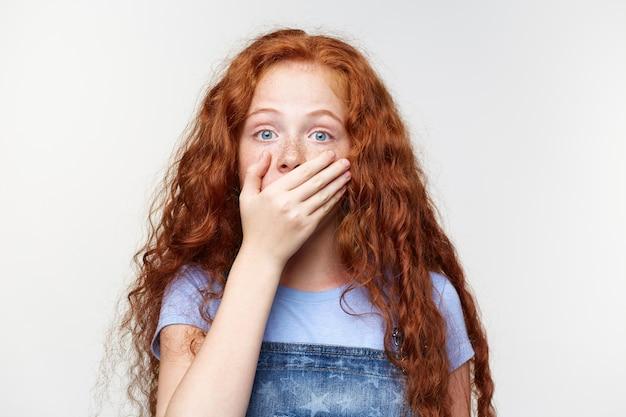 Ritratto di bambina lentigginosa carina scioccata con i capelli rossi, sente notizie incredibili, bocca coperta con la mano, si leva in piedi sopra il muro bianco con gli occhi spalancati con espressione sorpresa. Foto Gratuite