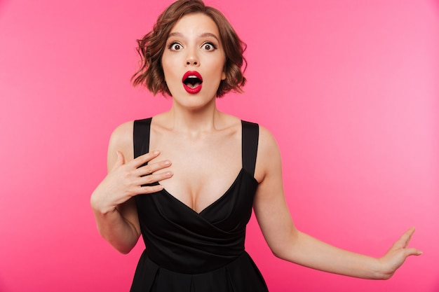 Portrait of a shocked girl dressed in black dress Free Photo