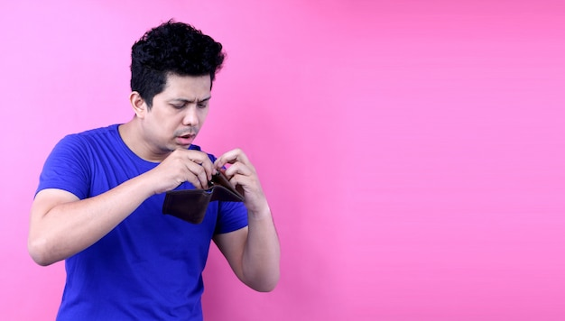 Portrait of a shocked, surprised speechless man asia, holding an empty wallet on pink background in studio Premium Photo