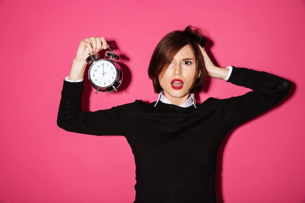 Portrait of a shocked upset businesswoman with alarm clock Free Photo