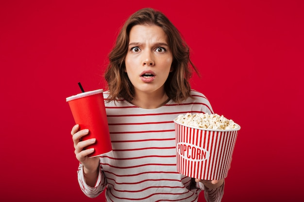 Portrait of a shocked woman holding popcorn Free Photo