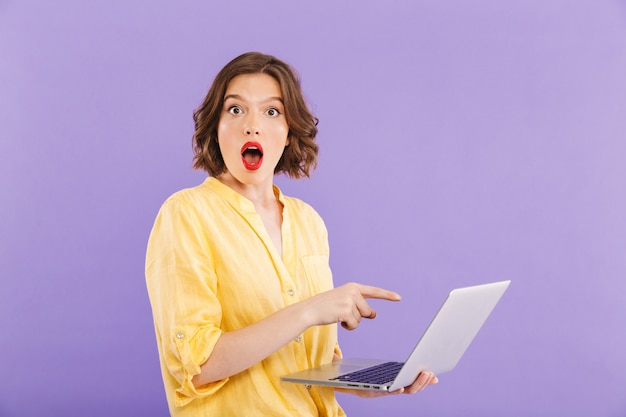 Portrait of a shocked young woman pointing at laptop Premium Photo