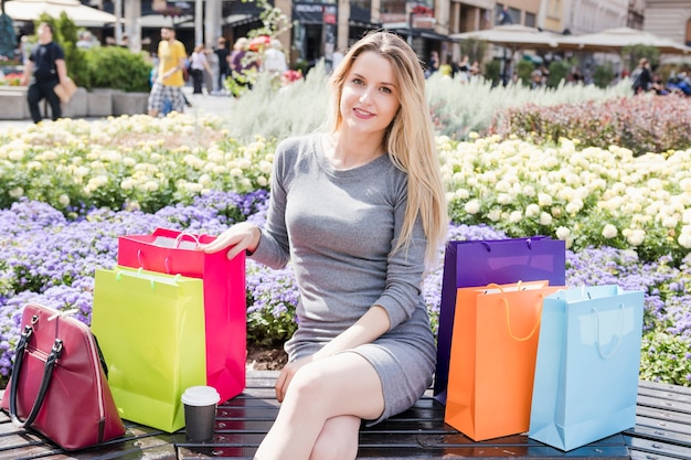 Portrait of a shopaholic woman with multi colored shopping bags Free Photo