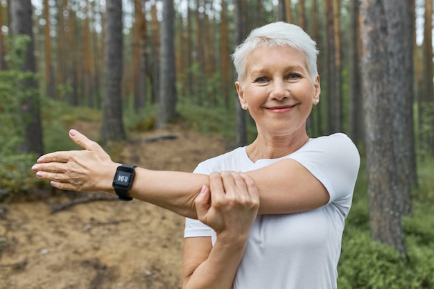 Portrait of short haired retired female wearing whit t-shirt and smart watch on her wrist to track progress during running Free Photo
