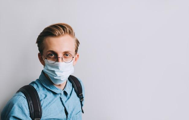 若い男のポートレートショット、バックパックを持つ大学生は透明な眼鏡と医療用使い捨てマスクを着用 Premium写真