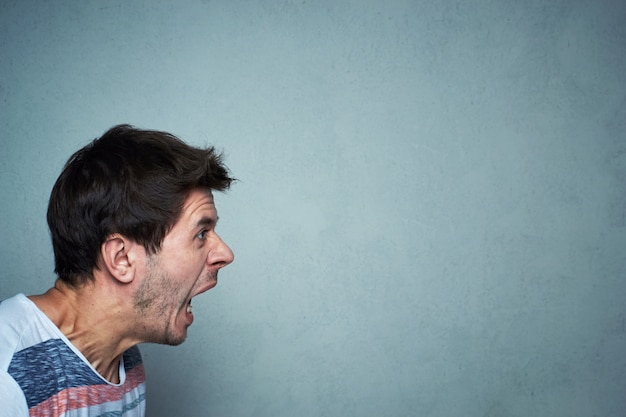 Portrait of shouting man at a gray wall background with copy space. screaming face Premium Photo