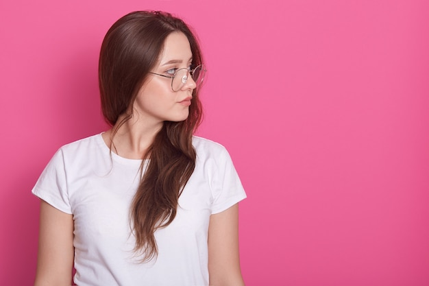 Portrait side profile of beautiful woman with long hair, dressed whitr casual t shirt and glasses, looking aside Free Photo