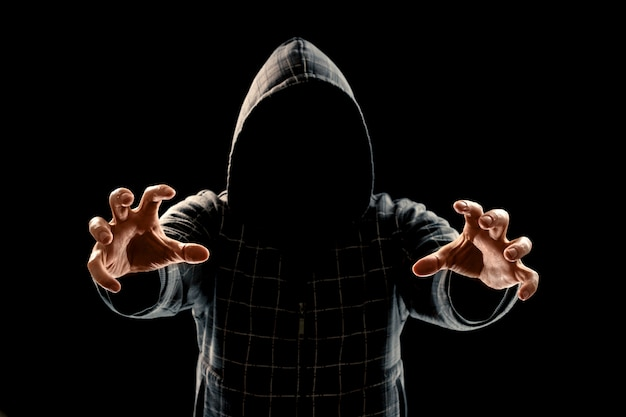Portrait silhouette of a man in a hood on a black background his face is not visible Premium Photo