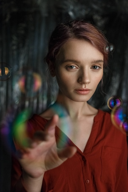 Portrait of skinny young caucasian girl in red shirt. soap bubbles fly around her head shimmering with rainbow colors. Premium Photo
